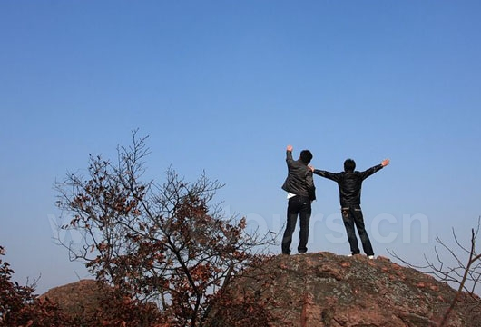 Two guys are cheering on the top of the mountain on Double Ninth Festival.