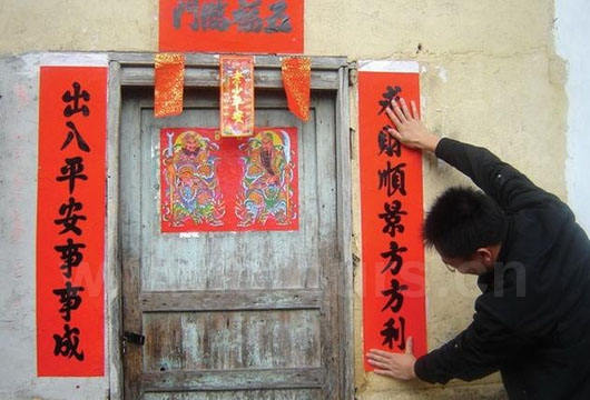 A young man in a small village was pasting spring festival couplet on three sides of the Gate to welcome Spring Festival on New Year's Eve.